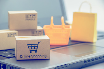 Shop online, ecommerce / retail commerce concept : Box or cartons with trolley or shopping cart, shopping basket on a laptop computer, depicts new lifestyle customers buy products via online store.