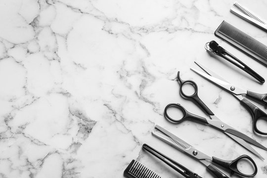 Flat lay composition with scissors and other hairdresser's accessories on white marble background. Space for text