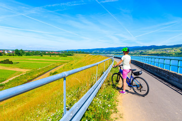 Young woman cyclist standing on cycling way along Czorsztynskie lake in Frydman village, Pieniny Mountains, Poland