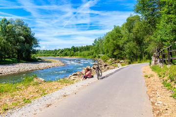 Unidentified woman cyclist sitting with bike on road near Dunajec river, Nowy Targ, Tatra Mountains, Poland