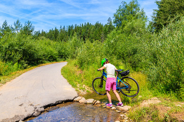 Young woman cyclist carrying bike over small stream near Dunajec river, Nowy Targ, Tatra Mountains, Poland