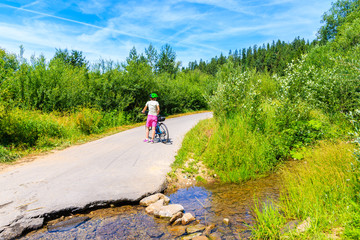 Young woman cyclist standing with bike on road near small stream by Dunajec river, Nowy Targ, Tatra Mountains, Poland