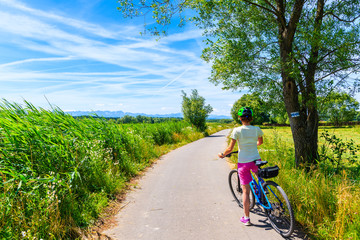 Fototapeta Young woman riding bike on cycling way along green fields near Czorsztynskie lake and Nowy Targ, Tatra Mountains, Poland obraz