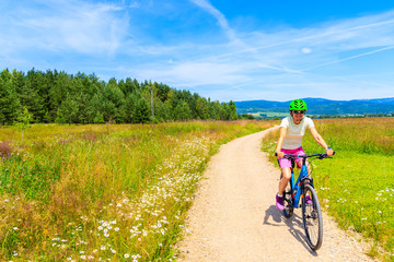 Young woman riding bike on cycling way around Tatra Mountains on sunny summer day, Poland