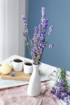 Beautiful lavender flowers in vase on table in room