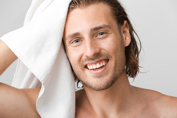 Handsome man wiping hair after washing against grey background