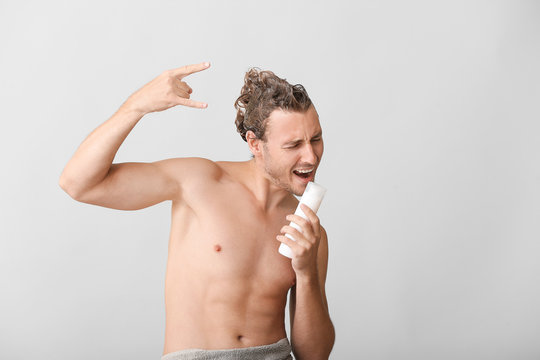 Handsome young man using bottle of shampoo as microphone against grey background