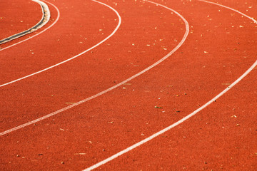 closeup of athletic red running tracks whit white lines and some leaves on it