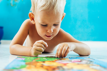 Excited boy with an educational puzzle