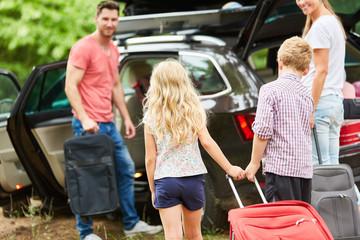 Familie am Auto beim Koffer packen