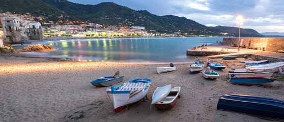 Panorama night shot of beautiful bay and fishing boats in Cefalu, Sicily, Italy