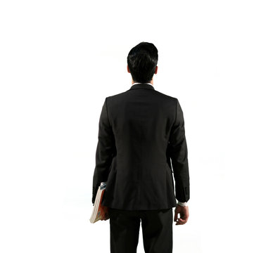 A man Standing against an empty wall wearing a Black suite and holding books | Teacher Back view