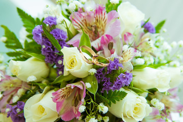 Beautiful delicate wedding bouquet of white roses and wedding rings of the bride and groom.