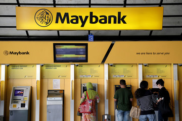 People use ATM machines at Maybank headquarters in Kuala Lumpur