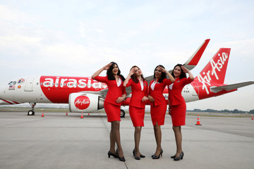 AirAsia crew members pose for a photograph in front of an Airbus A320 plane at Kuala Lumpur International Airport in Sepang
