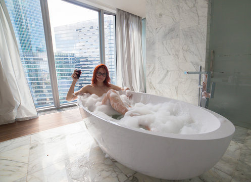 A ginger woman lying in the foam bath and hold a glass of red wine - a view on a modern glass buildings from the panoramic windows