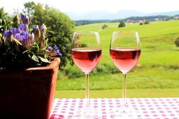 Zwei Weingläser mit Rosè, Enzian, Berge und Wiesen im Hintergrund, Allgäu, Bayern