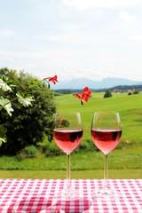 Zwei Weingläser mit Rosèwein, links Geranien, Landschaft mit Bergen im Hintergrund, Allgäu, Bayern
