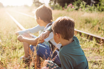 Group of children tweens on railway on sunset, summer time in country side