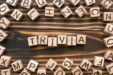 trivia - word from wooden blocks with letters, unimportant concept, random letters around, top view on wooden background