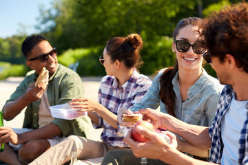 leisure and people concept - group of happy friends having picnic and eating sandwiches on lake...