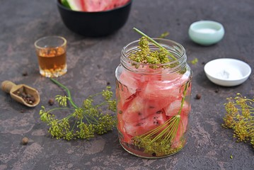 Cooking pickled watermelon in a glass jar on a dark concrete background. Canning, blanks. Watermelon Recipes