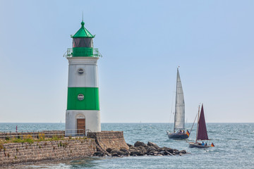 Sailboats passing by Schleimünde lighthouse between Schlei inlet and Baltic Sea