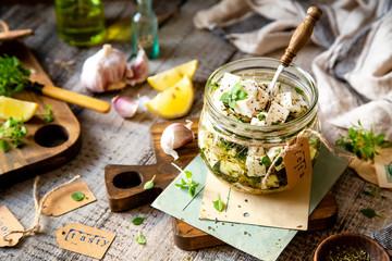 homemade marinated diced cheese feta in glass jar with herbs, garlic, basil