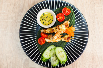 round plate with thai food on table chicken vegetables and sauce top view