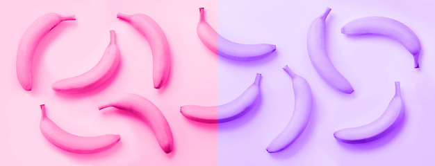 Chaotic colorful fruit pattern. Bananas over neon violet and pink color background. Banner. Top view. Pop art design, creative summer concept. Minimal flat lay style.