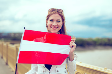 Young redhead woman holding Austrian flag on bridge