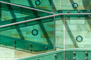 The details of modern architecture. Stairs in green, orange and yellow colors, made of stone, glass and metal.