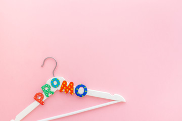 Wall Mural - White hangers with promo text on pink background
