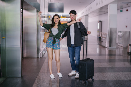 Portrait of a pair of young and excited Asian exchange students in a new country. One is a Korean man and the other an Indian girl. They are casually dressed and look excited in an airport.