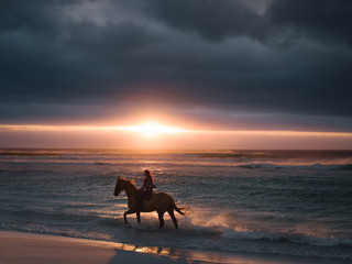Female riding horse along the beach