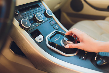 Close up Young woman hand on automatic gear shift, shifting gearbox in car.Driver woman hand holding automatic transmission or variable speed drive in car, shifting gear stick before driving car.