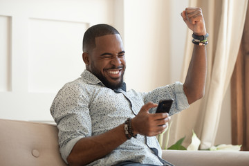 Overjoyed black man holding smartphone feeling euphoric with mobile win Fototapete