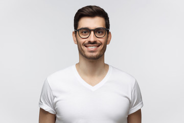 Smiling handsome young man in white t-shirt, looking at camera, isolated on gray background