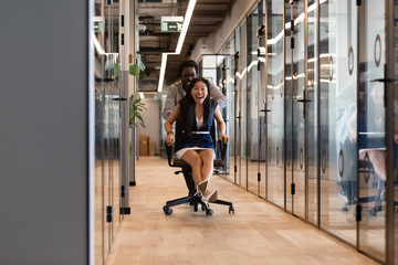 Excited diverse colleagues laughing riding on chair in office hallway