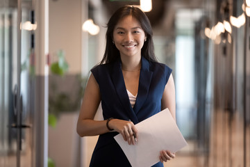 Happy asian businesswoman looking at camera stand in office hallway Fotomurales