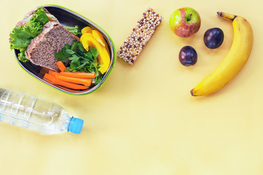 School lunch box with sandwich, vegetables, cereal bar and fruits on yellow background. Healthy food. Back to school concept.