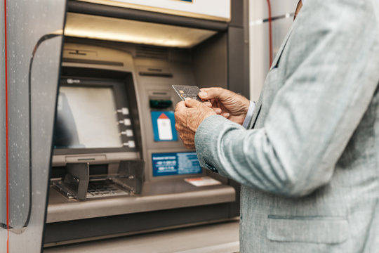 Close up shot of senior man hand using bank credit card. He typing pin code on keypad of ATM machine.