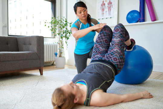 Chinese woman personal trainer during a workout session with an attractive blond client in a bright medical office