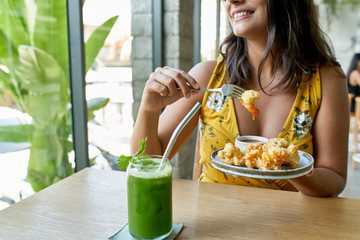 Lifestyle portrait of smiling healthy ethnic woman eating an organic plant-based cauliflower meal for vegetarians and drinking green smoothie