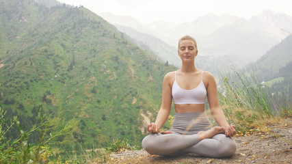 Sport girl doing yoga in mountains beautiful landscape. Young woman leads healthy lifestyle, meditates, relaxes lotus position in bright sportswear on nature