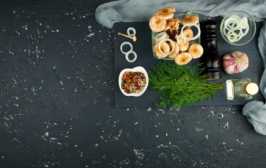 Fresh mushrooms with spices and herbs on black board. View from above. Copy space.