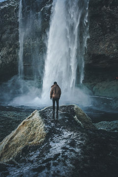 Man stands at the edge of trail in front of waterfall. Iceland