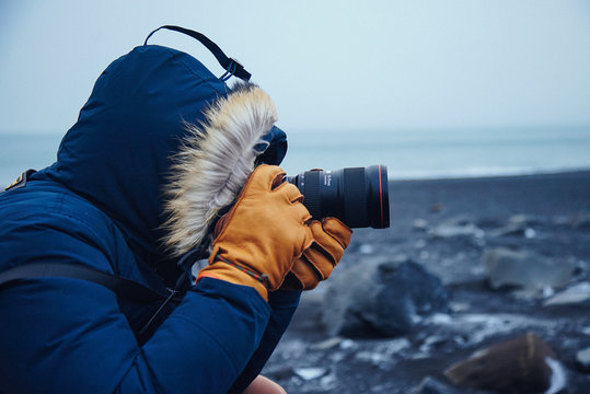 Photographer Takes picture on black sands beach with winter clothes.