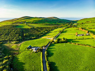 Spoed Fotobehang Lime groen Aerial view of endless lush pastures and farmlands of Ireland. Beautiful Irish countryside with green fields and meadows. Rural landscape on sunset.