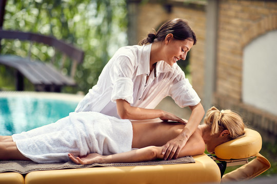 Young masseuse massages woman